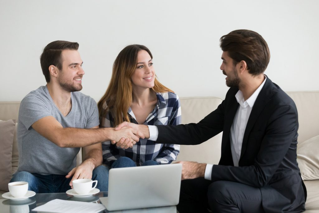 Happy family couple renters tenants handshaking realtor landlord at meeting
